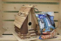 Ensemble d\'un nichoir en bois et d\'un sachet de graines pour oiseaux.